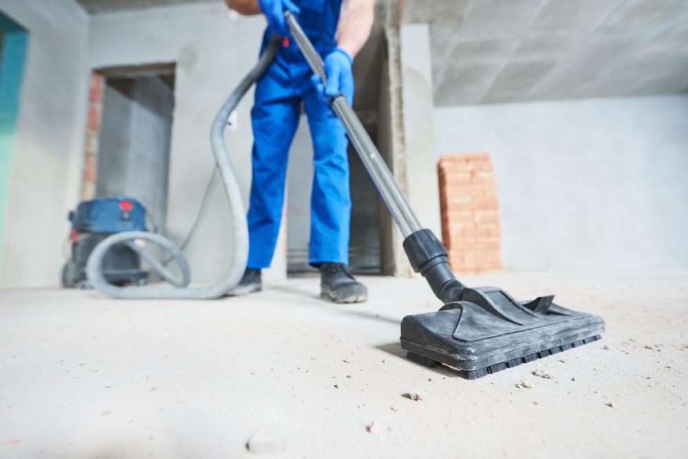 Hommesur un chantier aspirant des petits gravats avec un aspirateur industriel