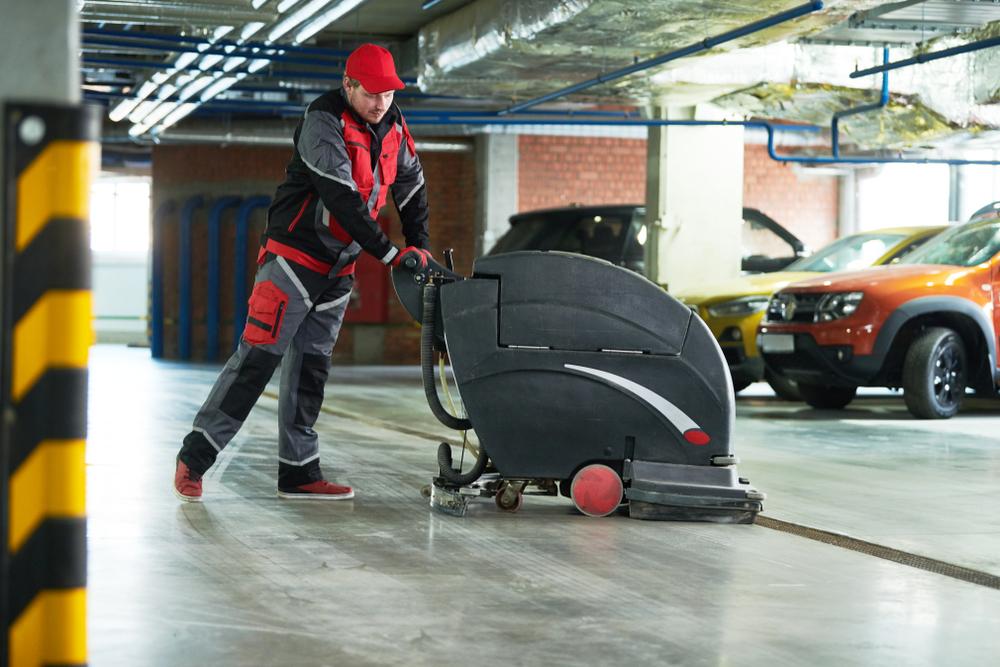 Homme nettoyant le sol d'un prking avec une autolaveuse accompagnée