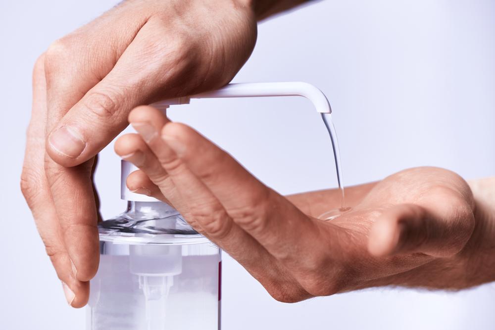 Jeune femme qui utilise un flacon doseur de gel hydroalcoolique et applique une dose de produit sur ses mains.